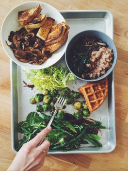 A hearty brunch of roasted and fresh greens and brussel sprouts, rosemary savory waffles, sauteed mushrooms n' onions with french toast, and collard greens with black eye peas grits.